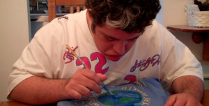 Teddy sitting at dining room table hand painting gandhi shirt