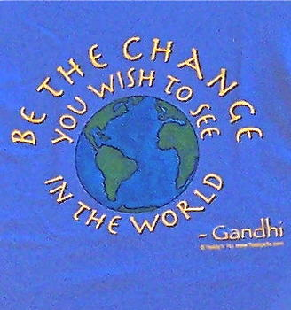 "Light blue shirt with gold lettering ""You must be the change…"" surrounding a hand drawn globe hand painted in blue and green by Teddy."