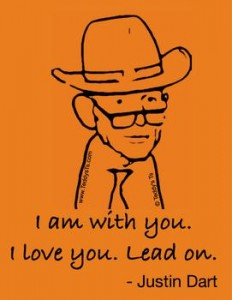 "Texas orange shirt says Justin Dart, Father of the ADA. There is a line drawing from a photo by Tom Olin and beneath the image  ""I am with you, I love you, Lead On"" ."